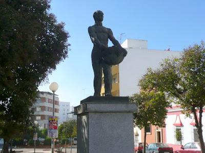 Estatua de un hombre que porta una cesta con uvas.