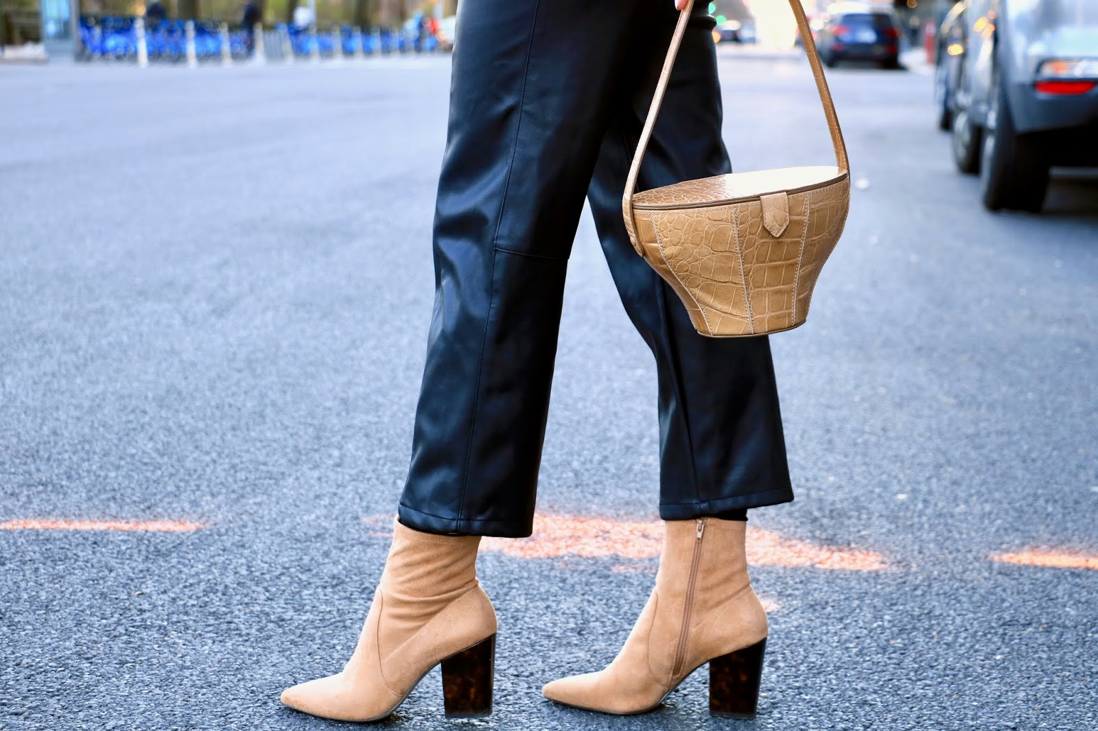Nyc fashion blogger Kathleen Harper wearing tan sock booties and a leather Staud purse.