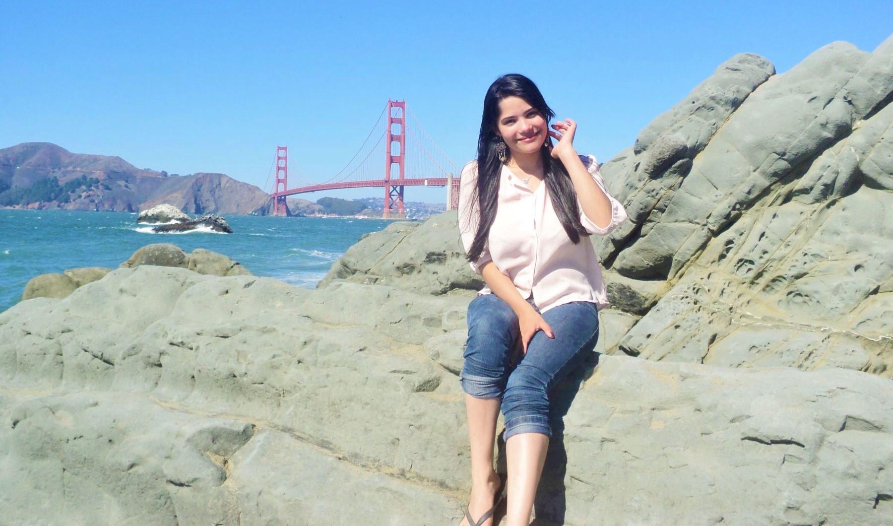 mulher sentada nas pedras de uma praia com a ponte golde gate ao fundo
