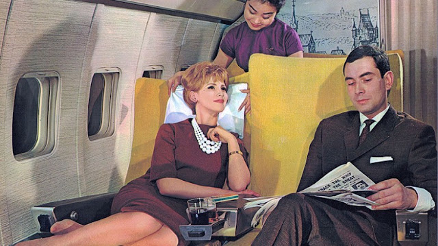 Flying in the fifties. Man in suit and woman in a dress, pearls and nylons