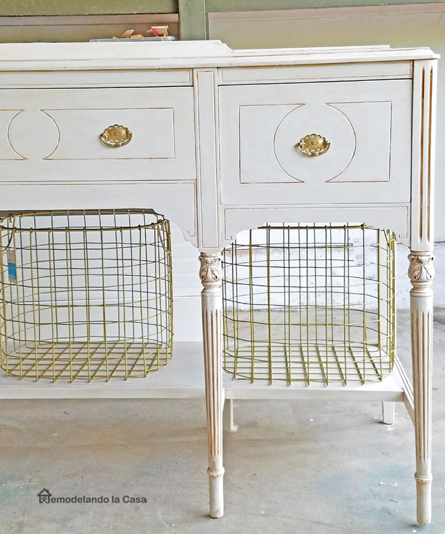 dark buffet painted white with gold hardware and metal bin baskets