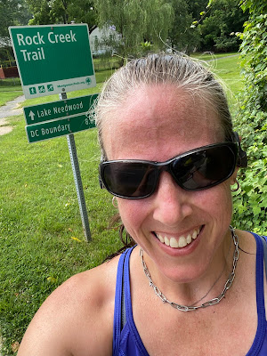 Selfie of me in front of a green sign for Rock Creek Trail.