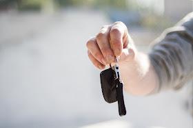 holding car key