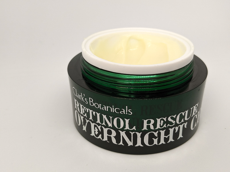 Jar of Clark's Botanicals Retinol Rescue Overnight Cream. The jar is dark green with white writing and the lid is off so the texture of the cream is visible - it is thick and off white