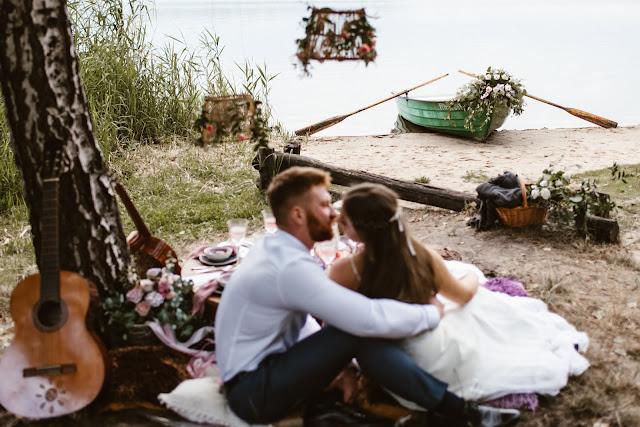 Stylizowana sesja zdjęciowa, Młoda Para w łodzi przystrojonej kwiatami, sesja zdjęciowa, romantyczny rejs, podróż poślubna, sesja ślubna, małżeństwo, talk about love, suknia ślubna, bukiet ślubny, pierścionek z kamieniem, pierścionek zaręczynowy, śliwki, fiolet, motyw przewodni, kolor przewodni, fioletowe wesele, lawendowe wesele, lawenda, śliwkowy, fiolet, stół, kieliszki, wino, tort