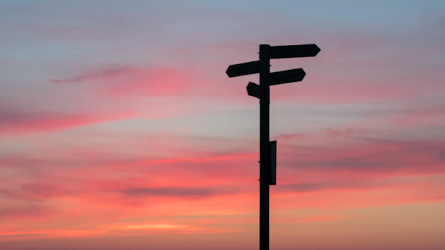 Signpost against a sunset