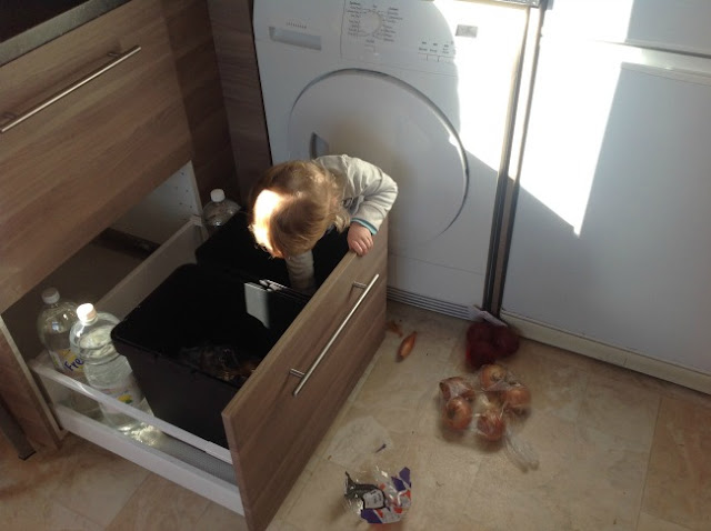 Toddler bent over in kitchen drawer, onions scattered across the foor