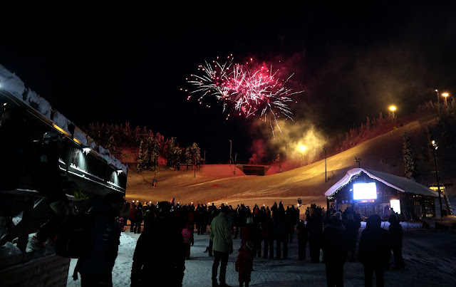 A group of people watching the fireworks on the ski slopes at Ruka