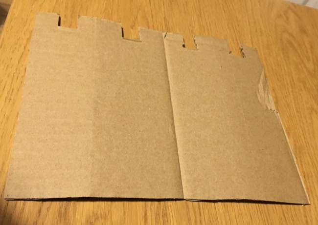 rectangle-of-cardboard-with-four-squares-cut-out-to-make-crenellations
