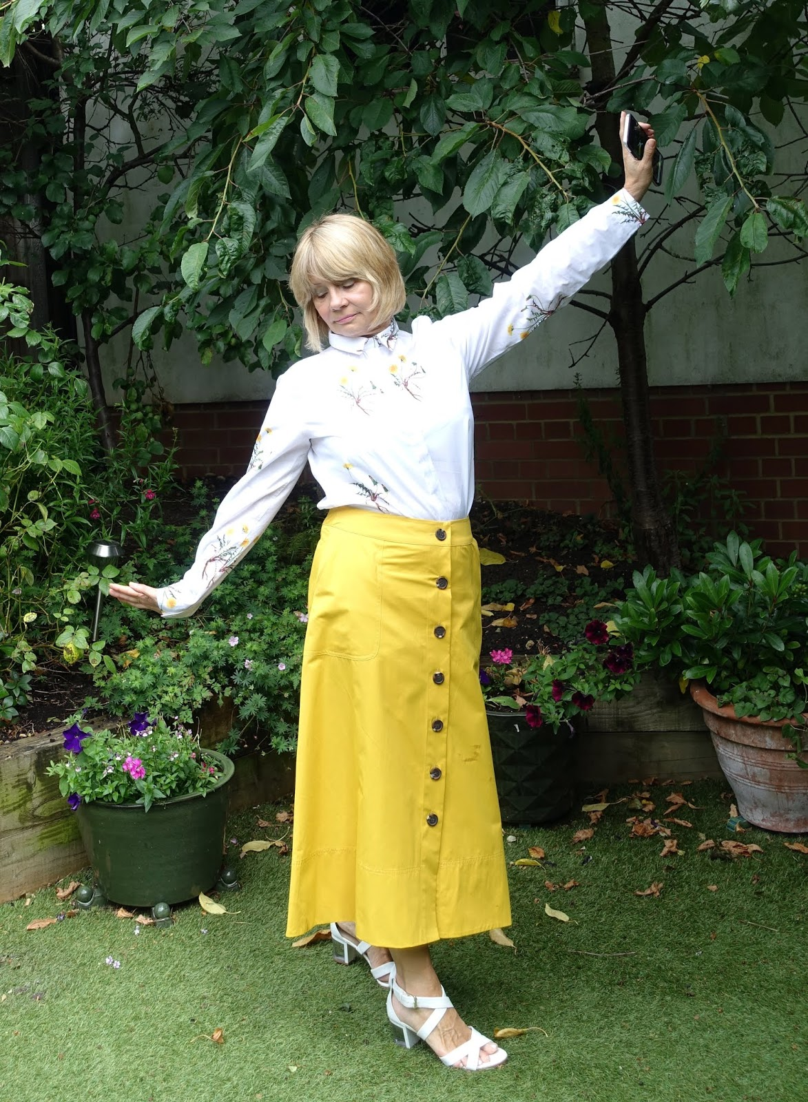 Over 50s woman in golden yellow midi skirt and white shirt with yellow flower print