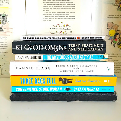 A stack of 7 books from top to bottom: No One Is Too Small to Make a Difference by Greta Thunberg, Good Omens by Neil Gaiman and Terry Pratchett, The Mysterious Affair at Styles by Agatha Christie, Fried Green Tomatoes at the Whistle Stop Cafe by Fannie Flagg, Three Bags Full by Leonie Swann, Convenience Store Woman by Sayaka Murata, a Kindle Fire with a black book cover