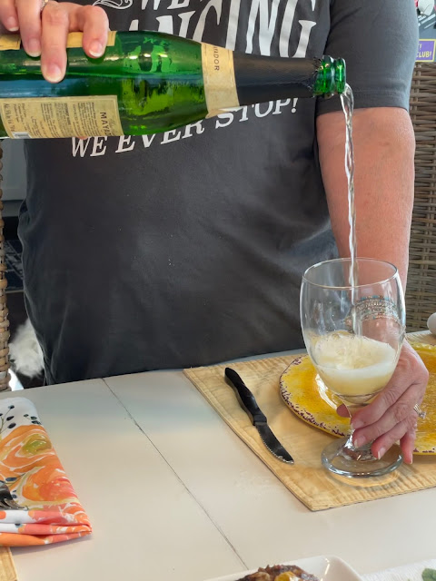 A tall stream of cider being poured into a glass.