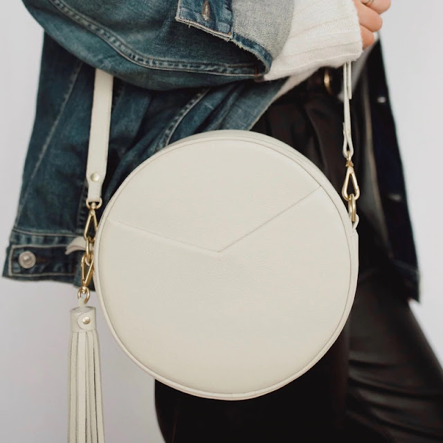 Woman holding cream circle bag from TAH bags
