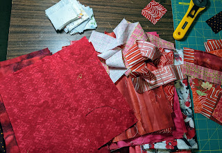 A small pile of red batiks and floral prints grouped on a table.