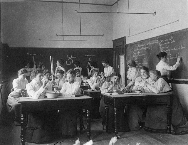 Group of young women performing atmospheric pressure experiments while studying science, circa 1890s