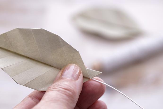 Close up Hand mit Origamiblatt und Drahtstiel