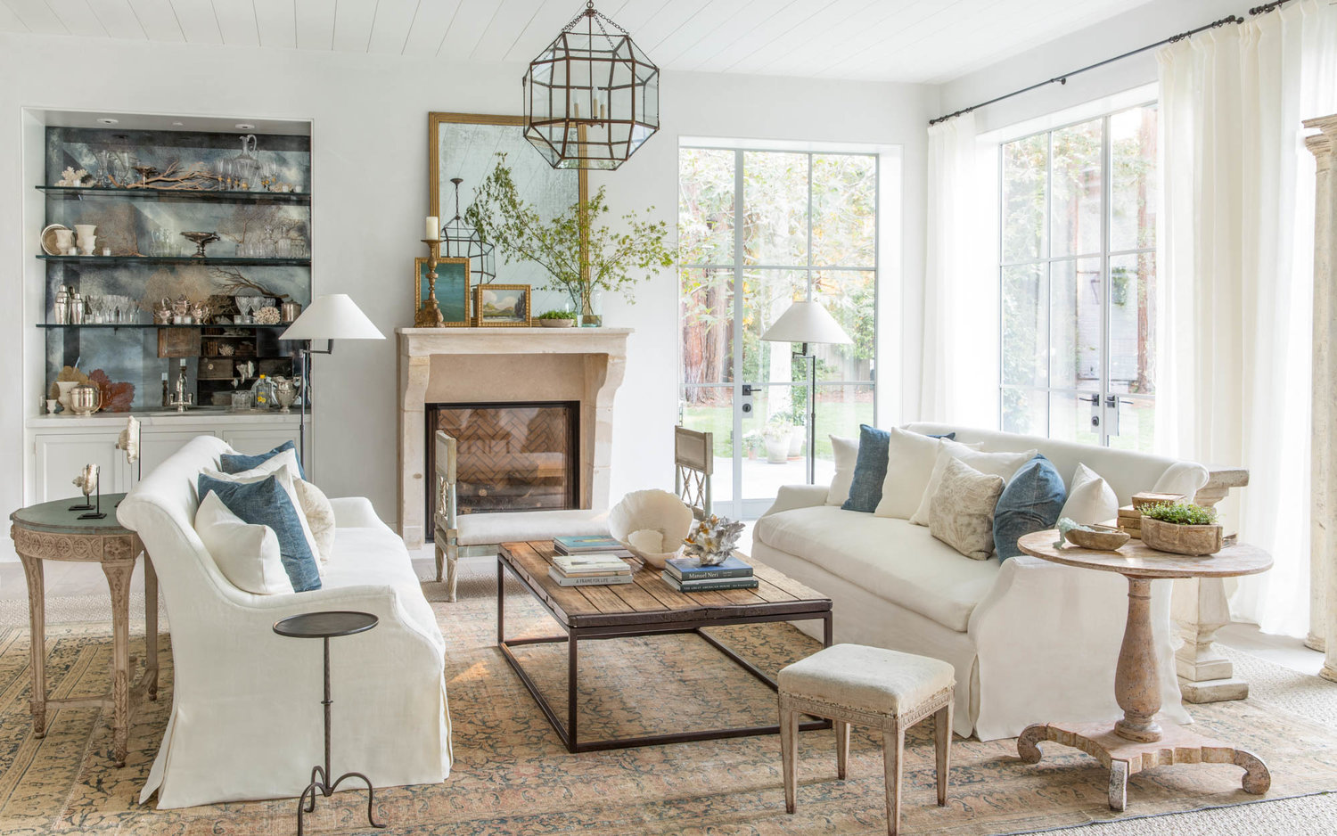 Living room with casual modern farmhouse style, Belgian linen, rustic tables, and limestone fireplace