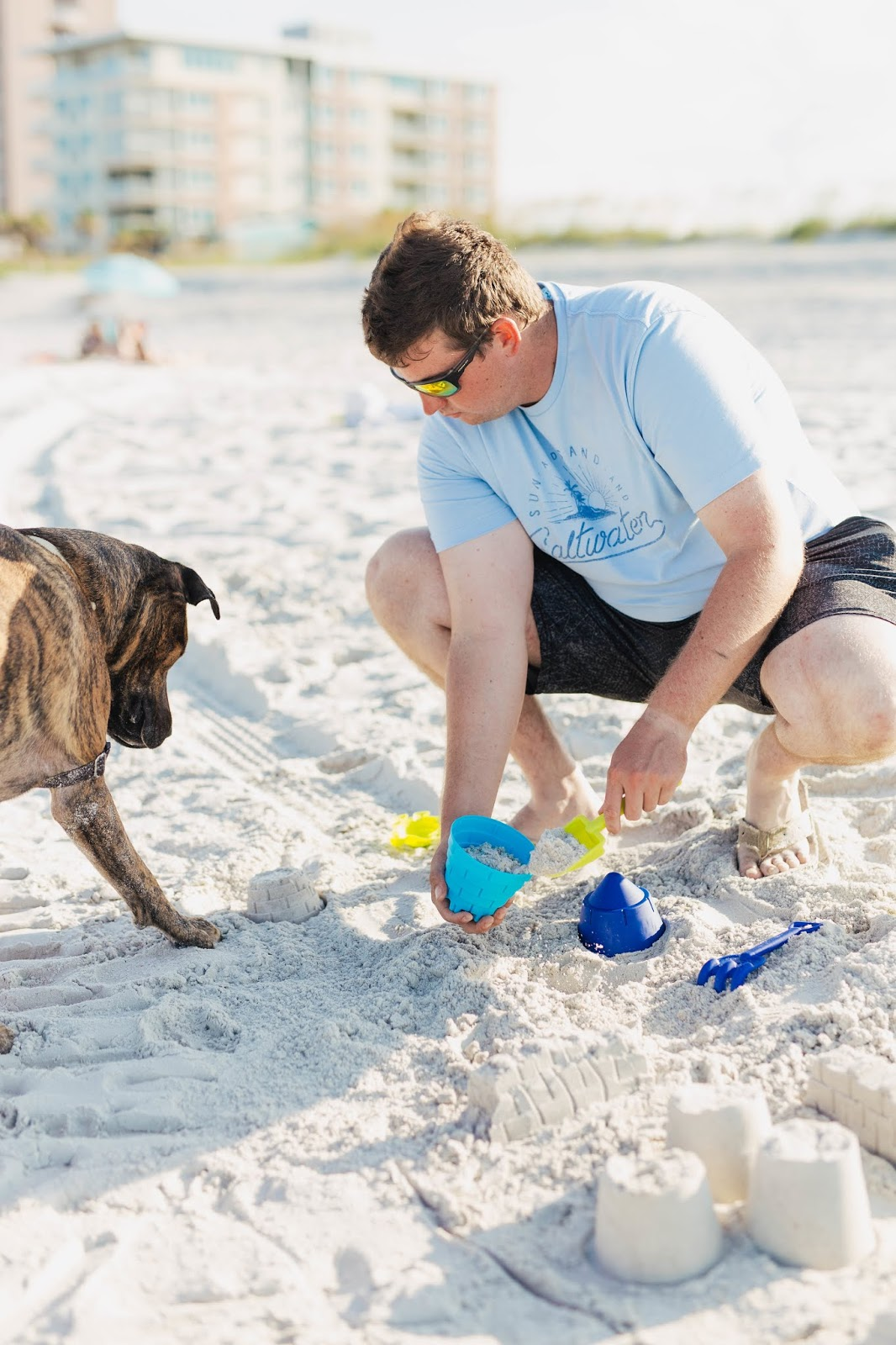man building sand castle on the beach