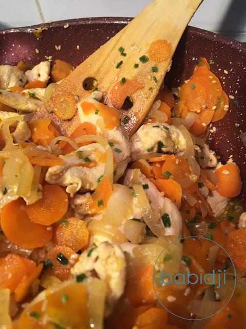 spatule en bois dans une sauteuse rempie de poulet sauté au sésame carottes oignons ciboulette et sauce soja