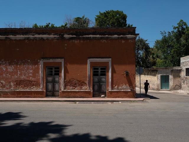 Silueta de un hombre al lado de una fachada colonial roja en Uayma