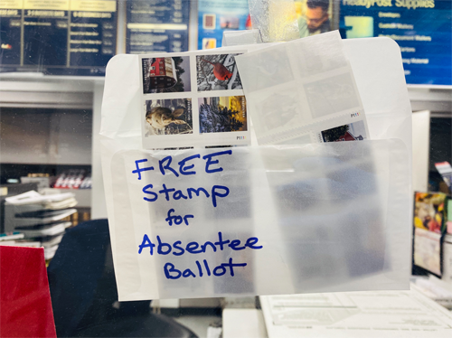 "photo, post office 2020, envelope with handwritten text: ""free stamp for absentee ballot"""