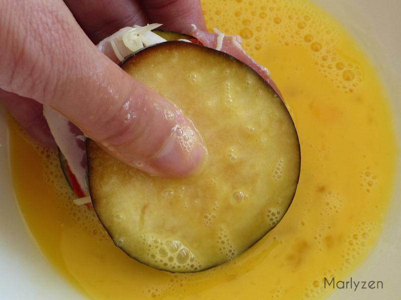 Trempez le sandwich d'aubergine dans les œufs battus.