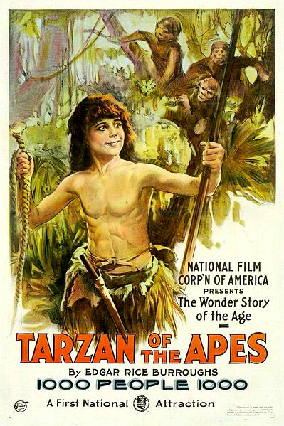 a bare-chested smiling boy is wearing a grass skirt and holding a rope in one hand and a pole in the other, as a group of monkeys looks on from the tree behind him