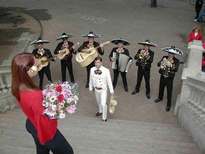 Mariachis dando serenata a una chica, que observa desde las escaleras con un colorido ramo de flores en la mano. Los músicos utilizan guitarras, trompetas y un guitarrón para interpretar la canción