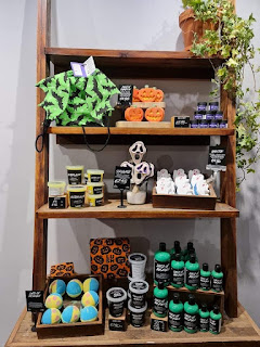 A shut of a light brown rectangular bookcase filled of different bath bombs, cylindrical plastic bottles and tubs filled with neon products and circular glass lids filled with coloured sugar with a plethora of portait black cards with white writing on them of the product names such as Lord of Misrule and bat art bath bomb on a bright background