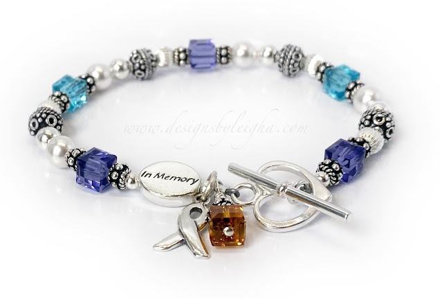 This suicide awareness bracelet is shown with turquoise and purple Swarovski crystals on the bracelet representing suicide awareness and an orange crystal symbolizing self-harm. I say a prayer for everyone whenever I make a Suicide Awareness Bracelet.