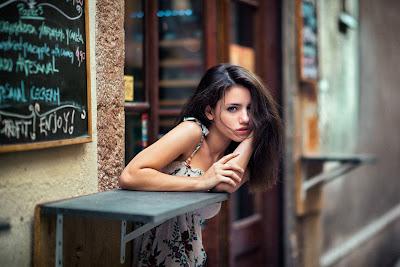 Chica sentada en cafetería mirando a cámara