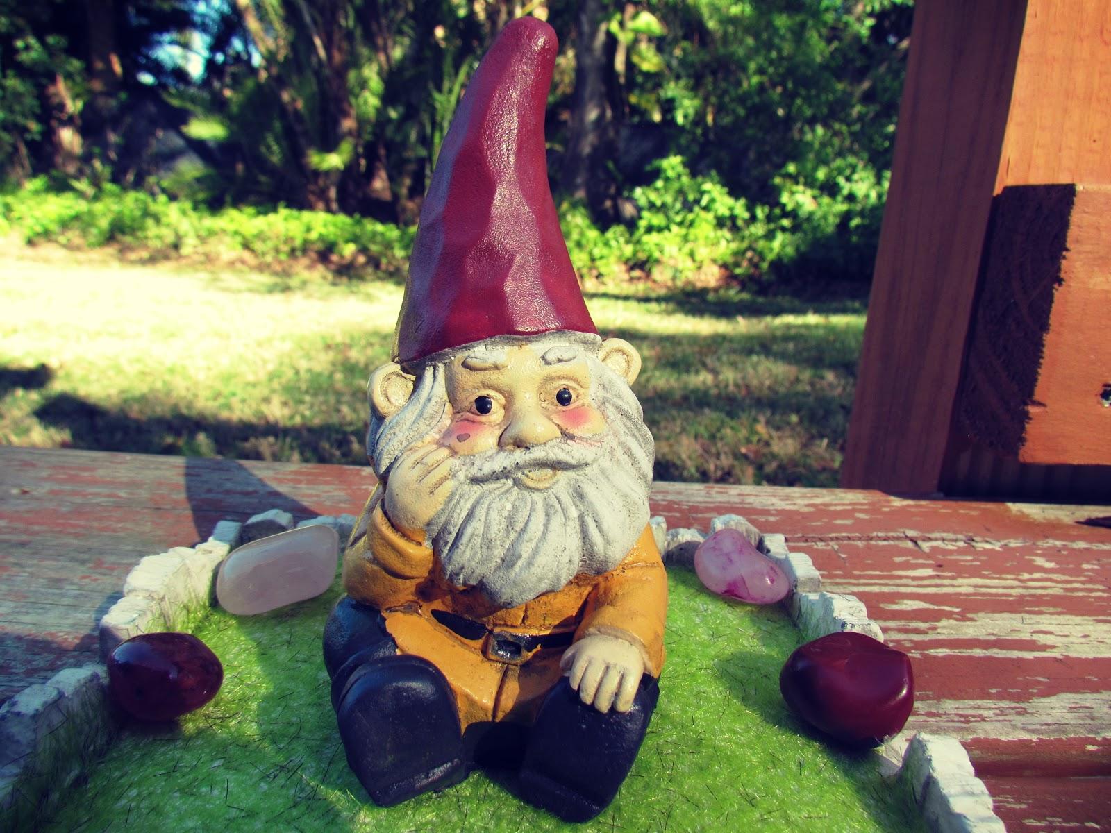 A garden gnome sitting in a green zen garden in the backyard in Florida + Florida Living