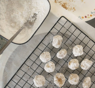 coating snowball cookies in powdered sugar