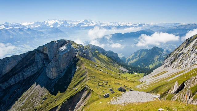 Hoge bergen met sneeuw. Op de berghellingen groeit gras.
