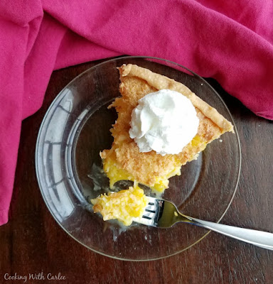 bite of coconut pineapple pie on fork with slice and whipped cream