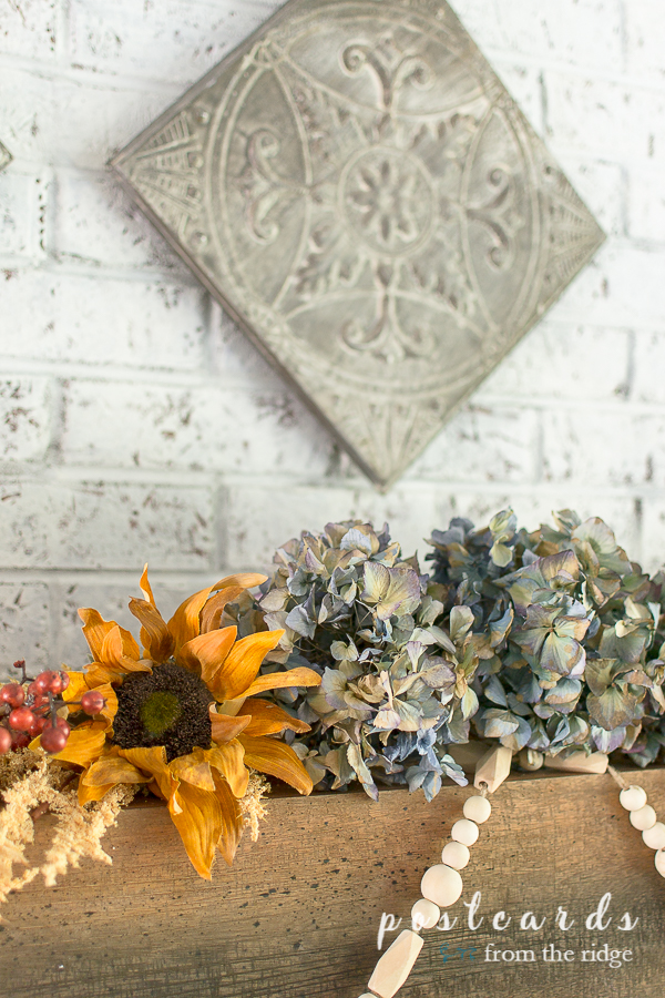 dried blue hydrangeas and sunflowers on wood fireplace mantel
