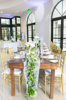 greenery centerpieces and farm table in reception