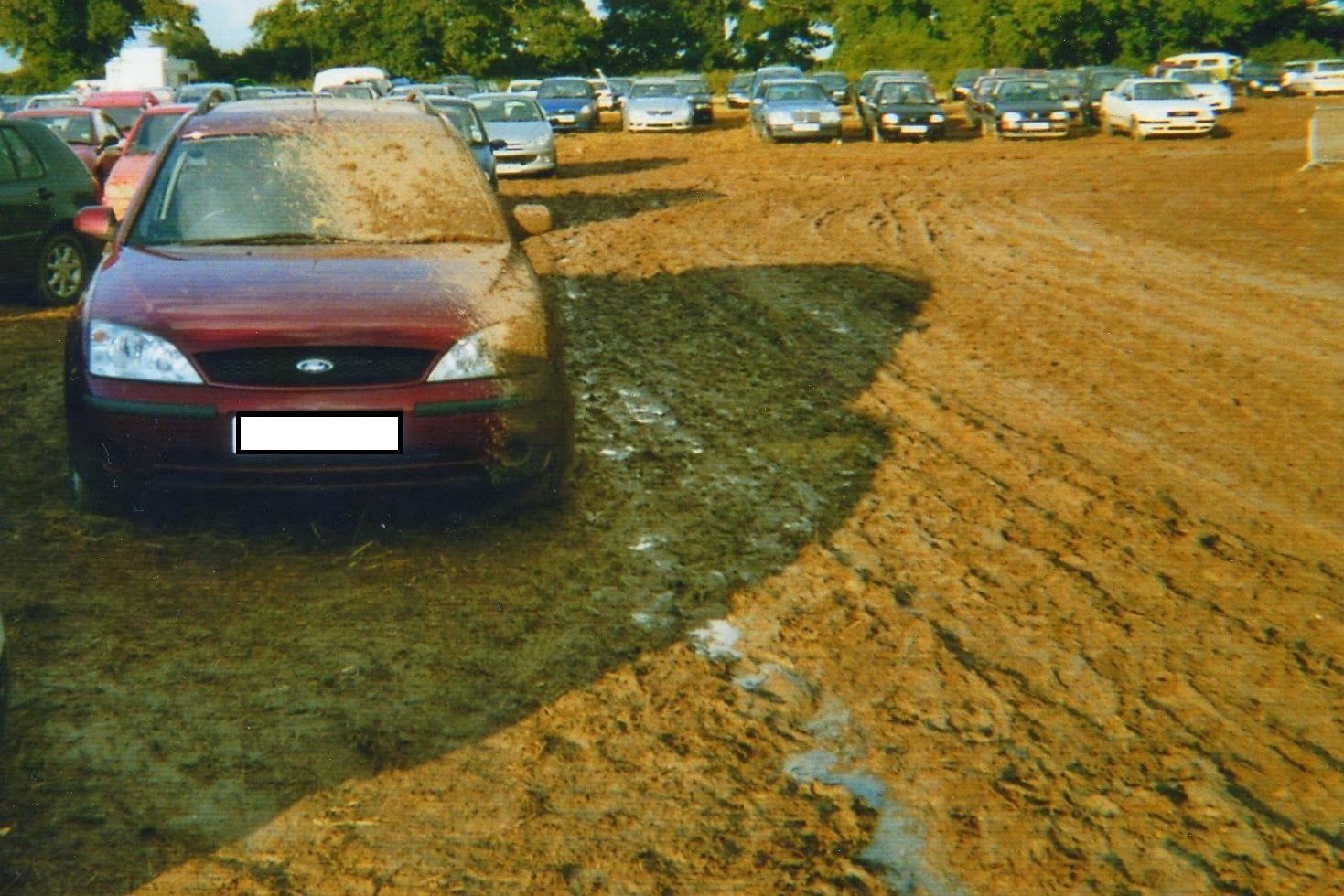 car covered in mud in  a festival car park