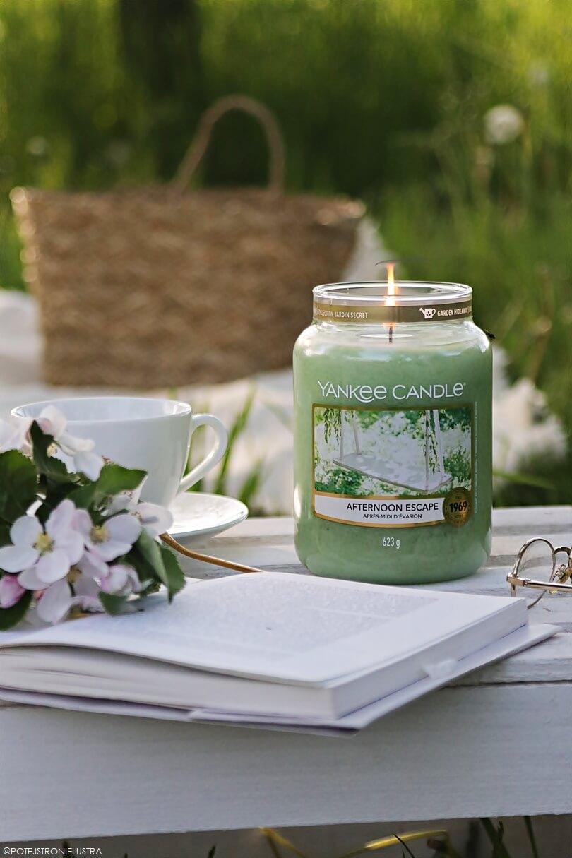 duża świeca zapachowa yankee candle afternoon escape w ogordzie na tle koca piknikowego, koszyka i zielonych drzew