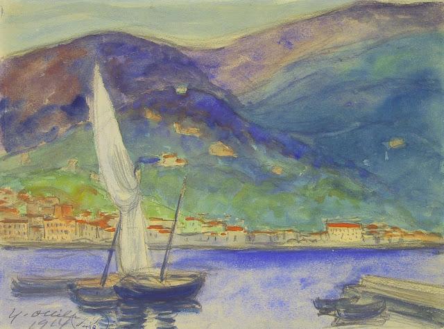 Purjevene Rivieralla: Purjeveneitä ja jollia satamassa. Taustalla punakattoisia vaaleita rakennuksia ja korkeat vuoret.