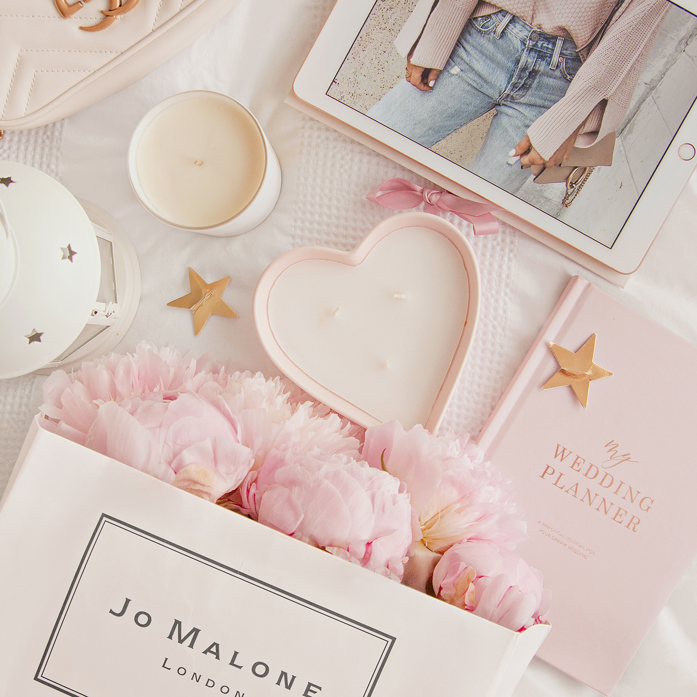 Flat lay image of a Jo Malone shopping bag filled with pink peonies