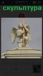 На крыше здания на шесте установлена скульптура ангела с крыльями за спиной