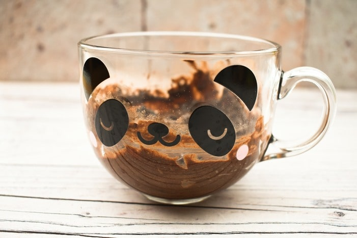 Side view of chocolate brownie in a clear mug with a panda face
