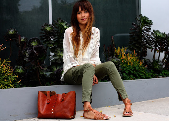 Девушка в белой блузе, джинсах и сандалиях гладиаторах