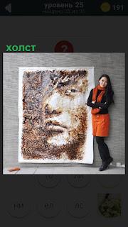 Девушка стоит около холста большого размера, на котором изображение лица