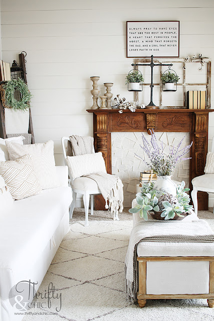living room with shiplap walls, rustic vintage fireplace mantel, blanket ladder, and white couch