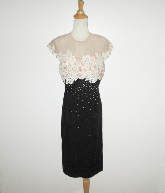1950's sheath style dress with black slim skirt and sheer bodice displayed on dress form