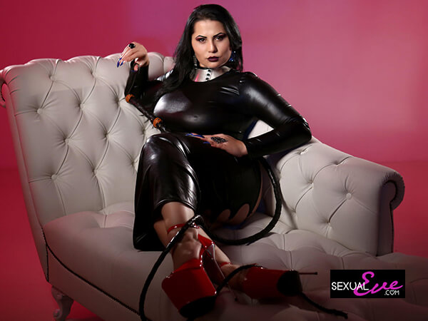 Black-haired Mistress in black wetlook dress and red high heels has black whip