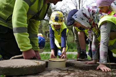 Barn i gula västar som gräver runt ett föremål i marken.