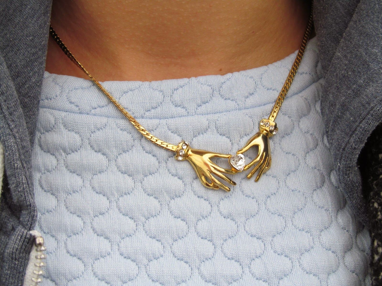 Gold chain with clasping hands